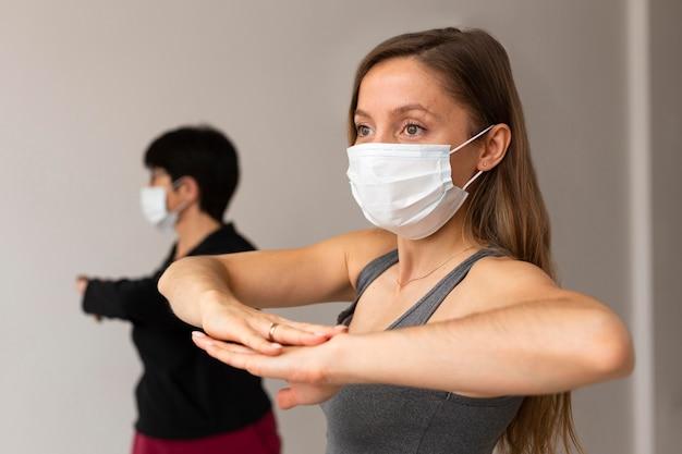 Mulheres se exercitando com máscaras