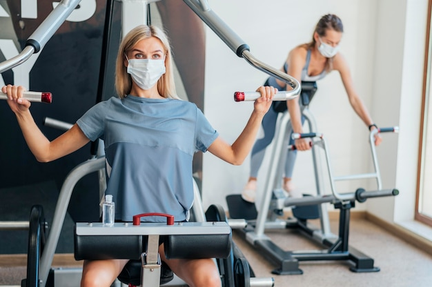 Mulheres se exercitando na academia com equipamentos e máscara