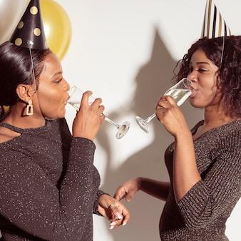 Mulheres se olhando enquanto bebem champanhe