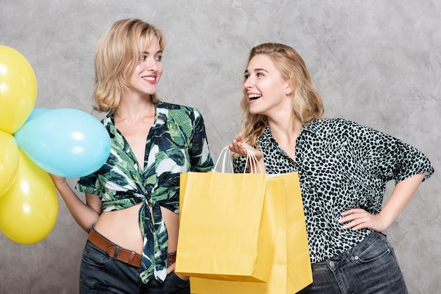Mulheres segurando balões e sacos de papel