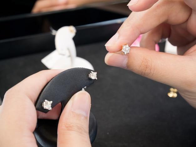 Mulheres segurando brincos de diamante em uma joalheria com diamantes