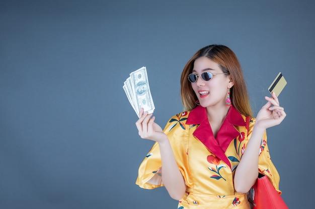 Mulheres segurando cartões inteligentes e dinheiro.