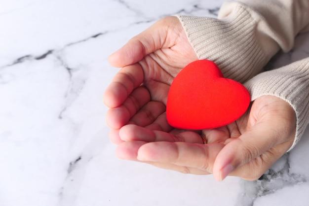 Mulheres segurando coração vermelho close-up.