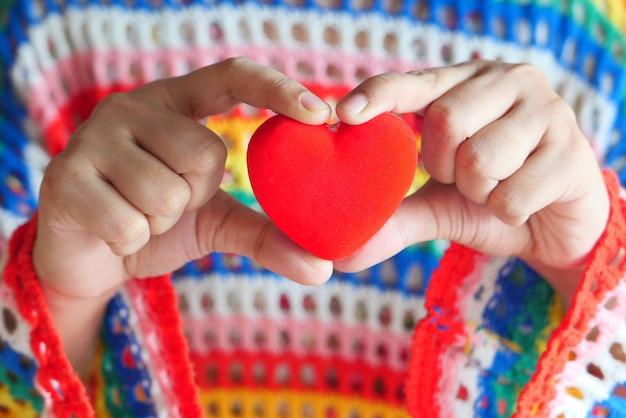 Mulheres segurando coração vermelho de perto