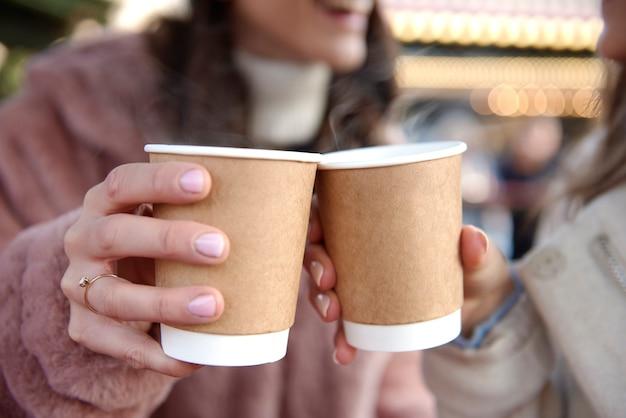 Mulheres segurando duas xícaras com vinho quente