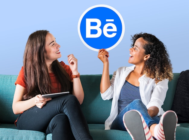 Mulheres segurando o logo do behance