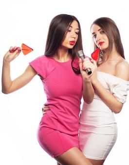 Mulheres segurando pirulito rosa e se divertindo juntas
