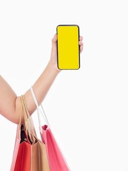 Mulheres segurando smartphone com tela em branco e sacolas de compras na parede branca