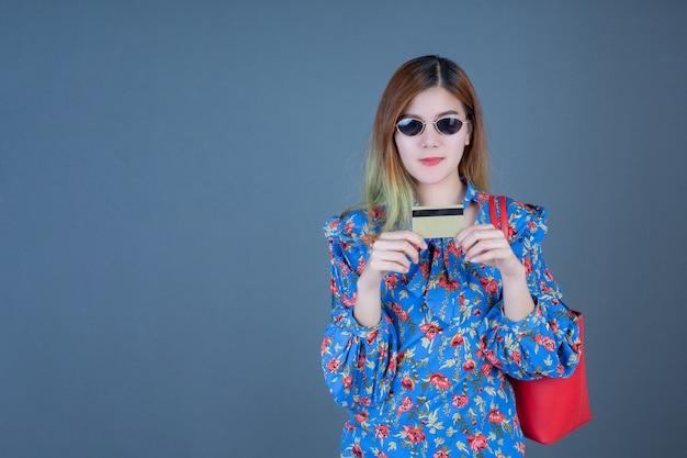 Mulheres segurando telefones e cartões inteligentes.