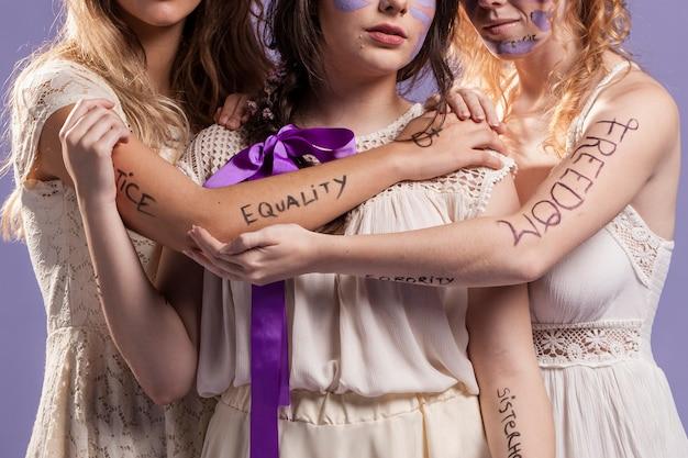 Mulheres segurando um ao outro enquanto pintado com palavras