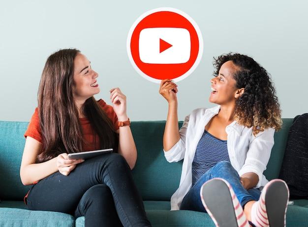 Mulheres segurando um ícone do youtube