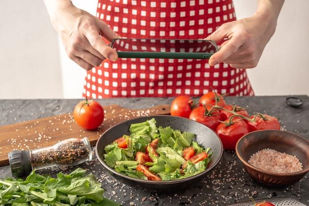 Mulheres segurando um telefone celular com uma bela salada de legumes apetitosa para tirar uma foto