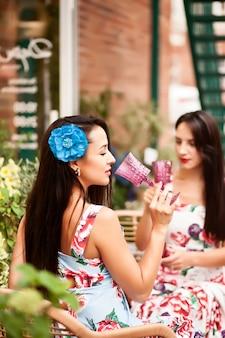 Mulheres segurando uma taça com vinho