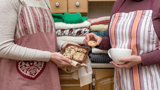 Mulheres segurando uma xícara de café e biscoitos vestidas com aventais festivos com muitos pulôveres diferentes na cozinha.