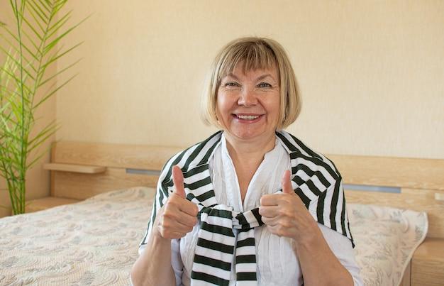 Mulheres sênior fazendo funky ação mulher de cabelos grisalhos, sorriso de meia-idade, mulher idosa usando óculos em casa, positiva solitária aposentada sênior mulher felicidade
