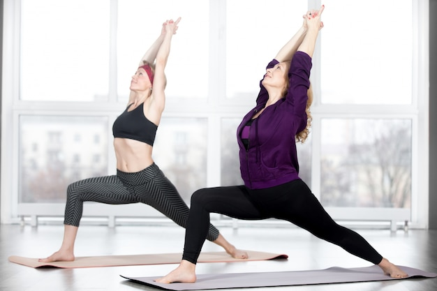 Mulheres sênior fazendo warrior 1 pose