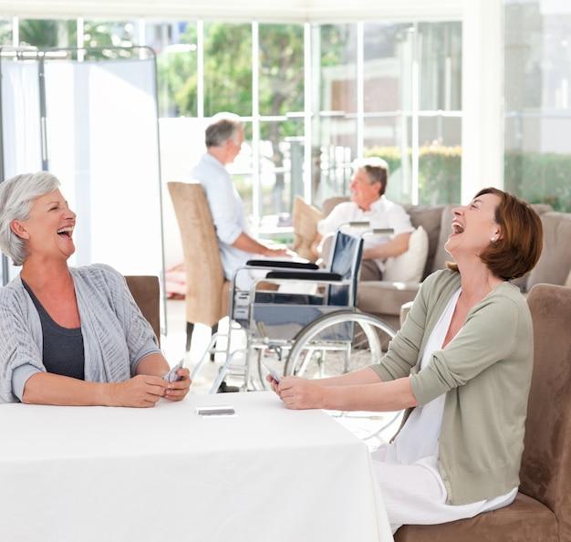 Mulheres sênior jogando cartas enquanto seus maridos estão falando
