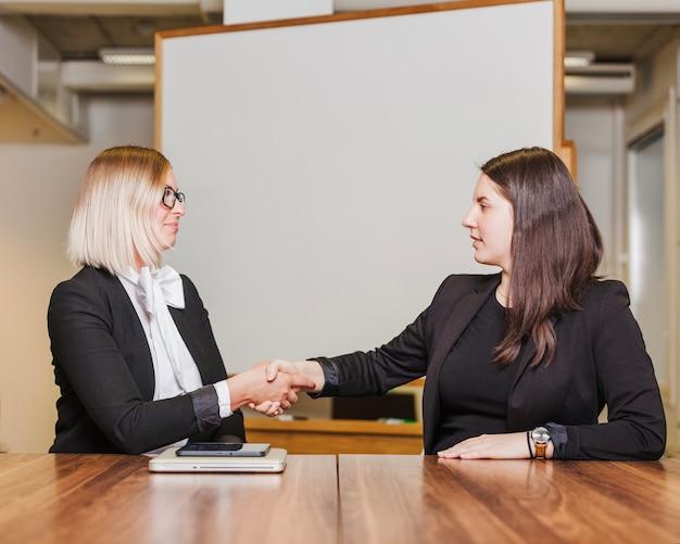 Mulheres sentadas à mesa apertando as mãos