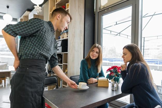 Mulheres sentadas à mesa com uma xícara de café e barista masculino