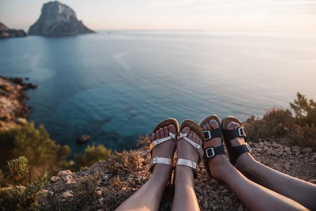 Mulheres sentadas em uma falésia à beira-mar apreciando a bela vista do pôr do sol