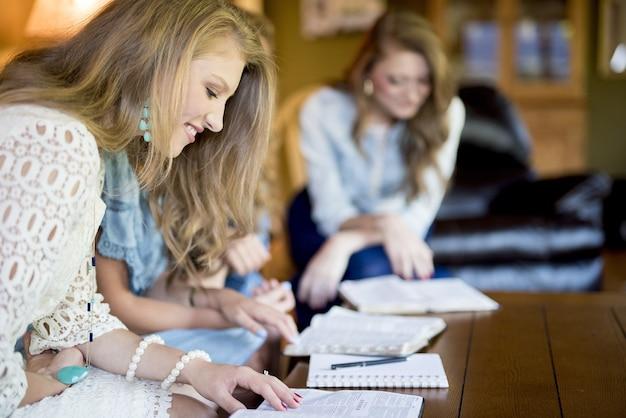 Mulheres sentadas lado a lado estudando em uma sala