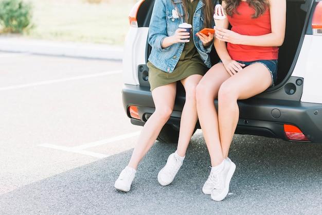 Mulheres sentadas na mala do carro no estacionamento