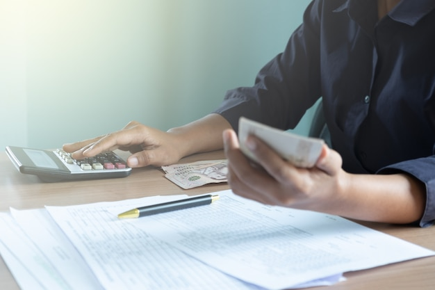 Mulheres sentadas na mesa usando calculadora e segurando o dinheiro