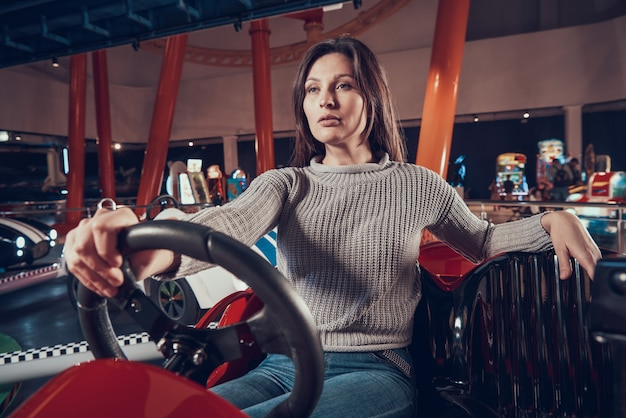 Mulheres sentadas no carro de brinquedo no centro de diversões.