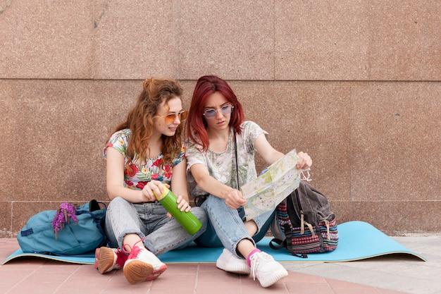 Mulheres sentadas no chão olhando o mapa