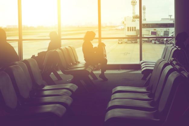 Mulheres sentam-se no banco em um átrio do aeroporto à espera de voo
