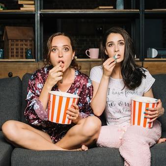 Mulheres, sentando, ligado, sofá, olhar fixamente, enquanto, olhando televisão