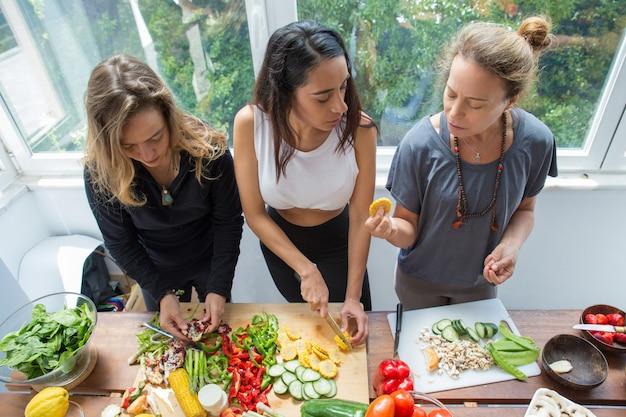 Mulheres sérias conversando e cortando legumes na cozinha