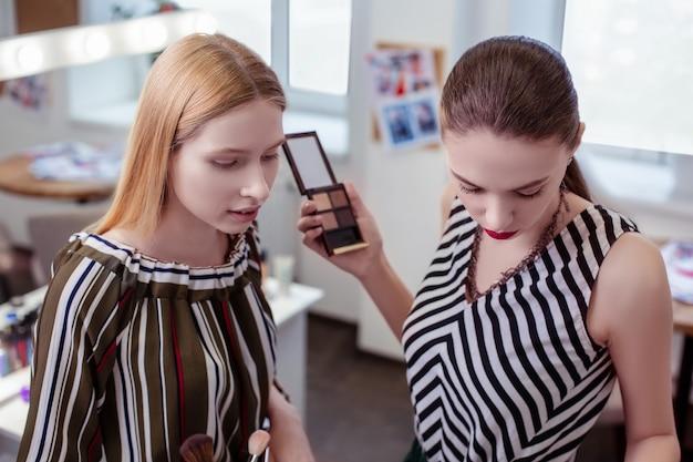 Mulheres sérias e agradáveis juntas enquanto escolhem cosméticos para si mesmas