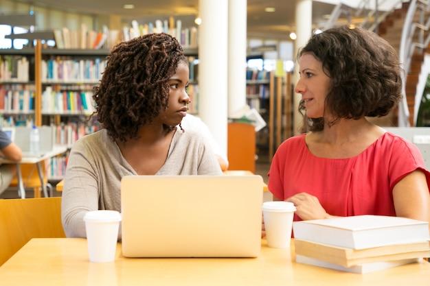 Mulheres sérias, sentado à mesa e usando o laptop
