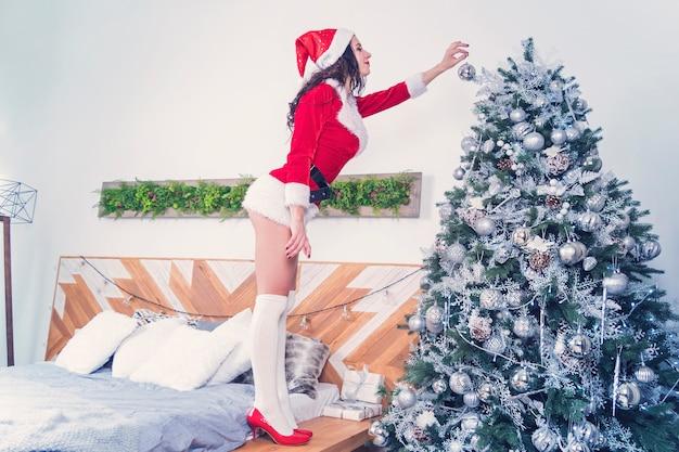 Mulheres sexy com a roupa do papai noel segurando uma bola de natal para a árvore de natal. garota sexy decora o apartamento para celebrar o ano novo e o natal em um quarto com design moderno.