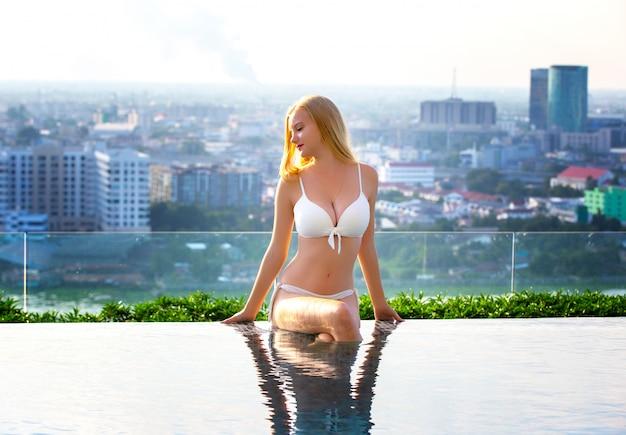 Mulheres sexy com biquíni branco, relaxar-se à beira da piscina