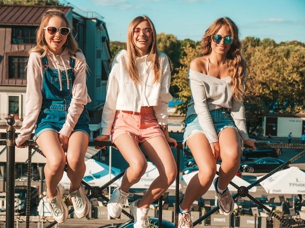 Mulheres sexy, sentado no corrimão na rua. modelos positivos se divertindo em óculos de sol. eles se comunicando e discutindo algo
