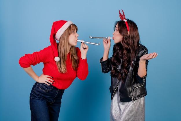 Mulheres, soprando chirstmas assobios e usando chapéu de natal isolado sobre o azul