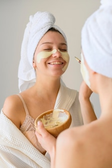 Mulheres sorridente, aplicar máscaras em casa