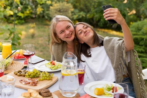 Mulheres sorridente em tiro médio tirando selfie