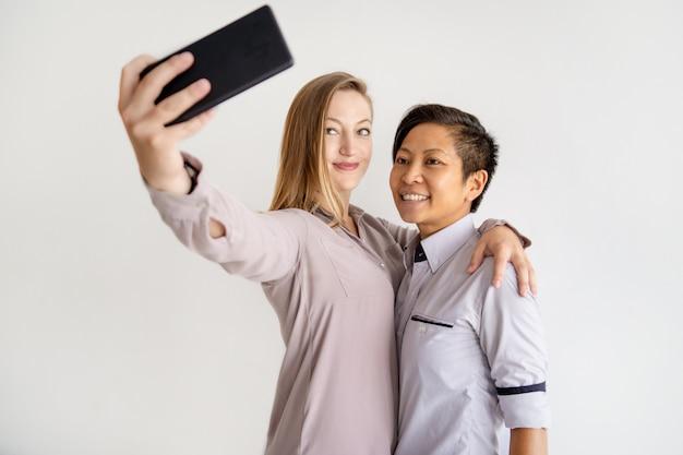 Mulheres sorridentes, abraçando e tirando foto de selfie