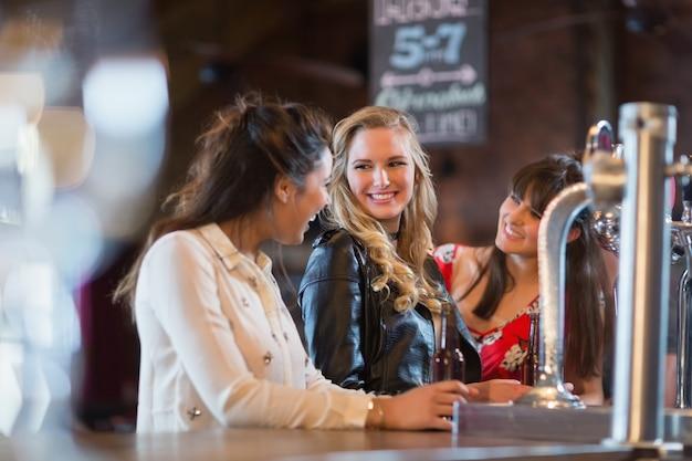 Mulheres sorridentes ao lado do balcão do bar