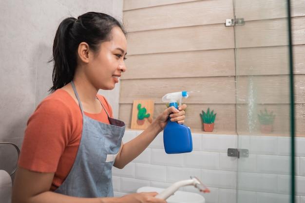 Mulheres sorridentes borrifam usando um borrifador de garrafas e seguram os limpadores de vidro enquanto limpam o vidro do banheiro