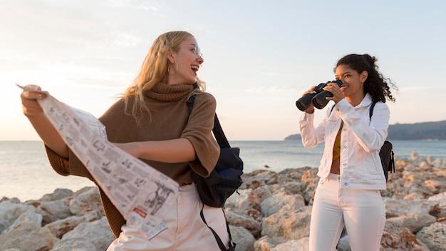 Mulheres sorridentes com mapa e binóculos