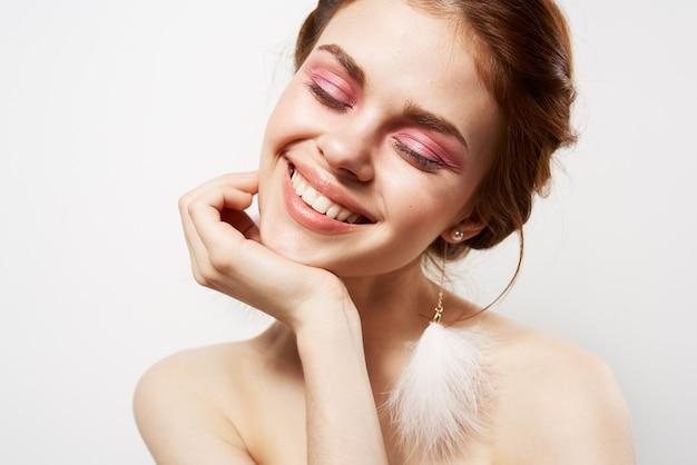 Mulheres sorridentes com ombros nus e brilhantes brincos de maquiagem close-up