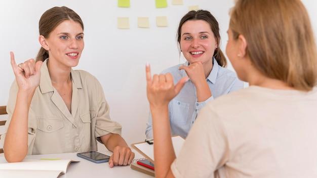 Mulheres sorridentes conversando à mesa usando linguagem de sinais