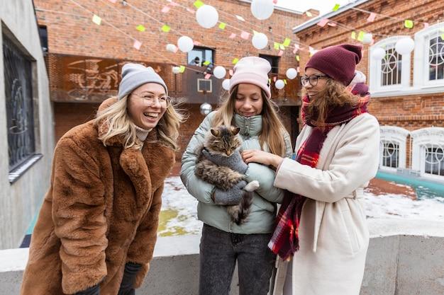 Mulheres sorridentes de tiro médio com gato