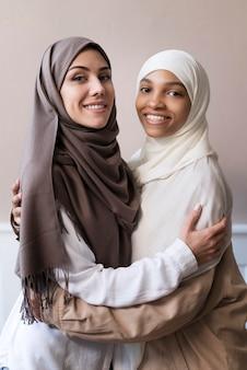 Mulheres sorridentes de tiro médio com hijab