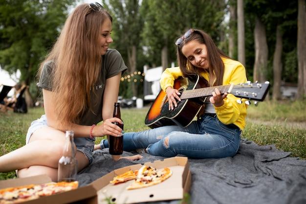 Mulheres sorridentes de tiro médio com violão