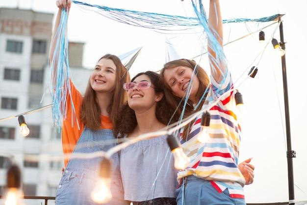 Mulheres sorridentes de tiro médio na festa